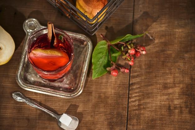 Glas cider-perencocktail of limonade, kaneelstokjes, anijssterren op houten oppervlak.