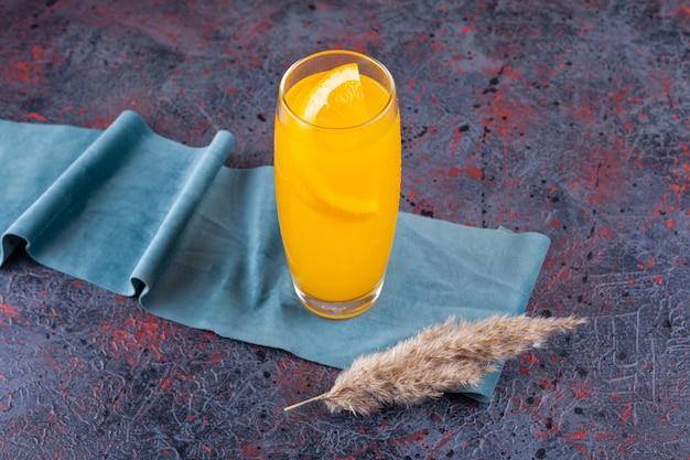 Glas citroensap met gesneden citroen op blauw.