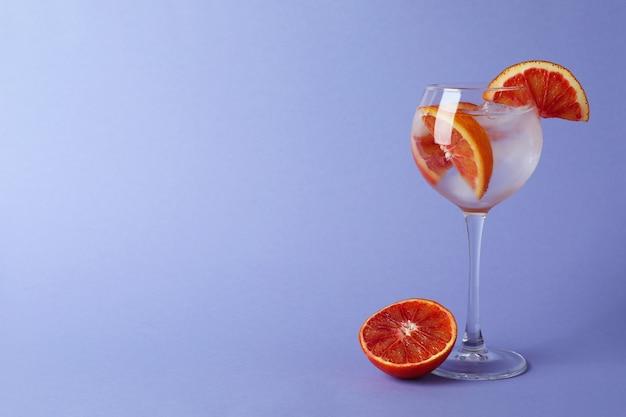 Glas cocktail met grapefruit op violet oppervlak