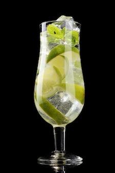 Glas cocktail met limoen en munt op zwart