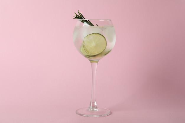 Glas cocktail met limoen op roze oppervlak