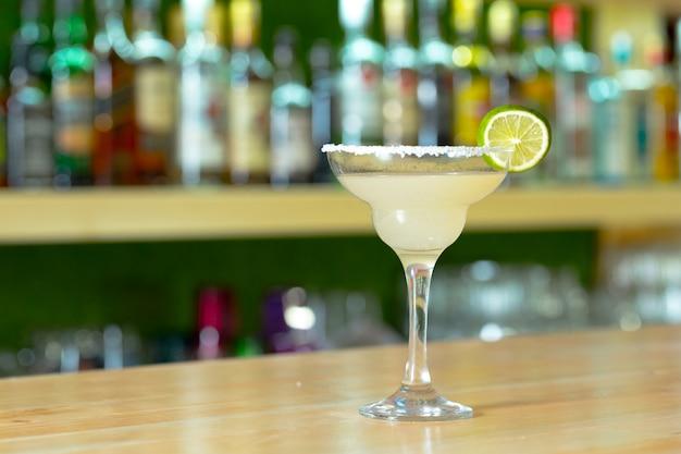 Glas cocktail met vruchten bij barteller wordt verfraaid die.