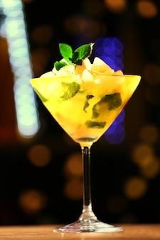 Glas cocktail op donkere vage lichtenachtergrond