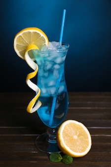 Glas cocktail op tafel op donkerblauwe achtergrond