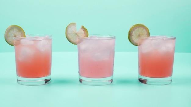 Glas cocktaildrank met citroenplak en ijsblokjes tegen muntachtergrond