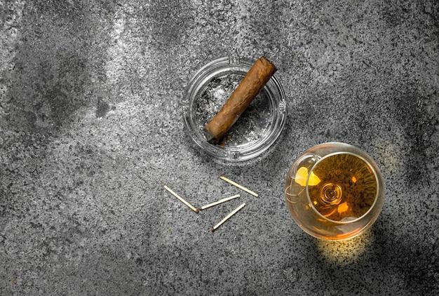 Glas cognac met een sigaar. op een rustieke achtergrond.