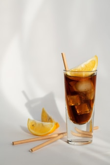 Glas cola met ijs, citroen en stro op een witte achtergrond