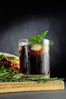 Glas cola met ijs, munt en rozemarijn op zwarte grote sandwich als achtergrond, straatvoedsel