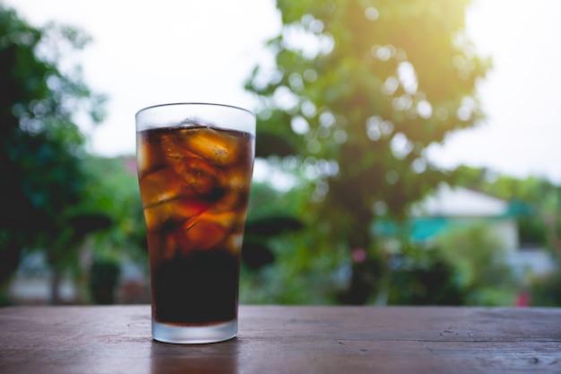Glas cola met ijs op tafel.