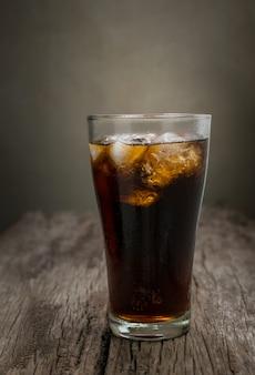 Glas cola met ijsblokjes op houten lijst, frisdrank.