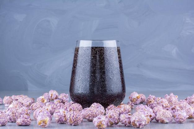 Glas cola omgeven door verspreide popcorn snoep op marmeren oppervlak
