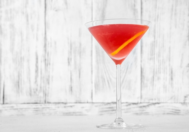 Glas cosmopolitan cocktail gegarneerd met een citroenschil
