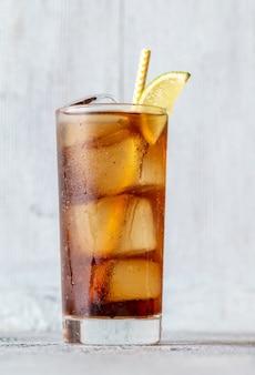 Glas cuba libre-cocktail met limoenwig