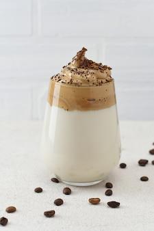 Glas dalgona fluffy slagroom op witte achtergrond met koffiebonen.