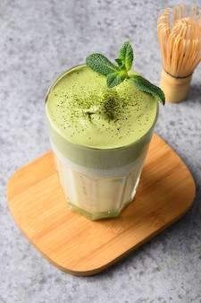 Glas dalgona iced matcha thee en bamboe op grijs. verticaal formaat. detailopname.
