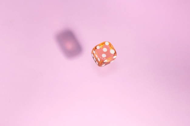 Glas dobbelstenen vallen, bot naar spel op roze achtergrond.