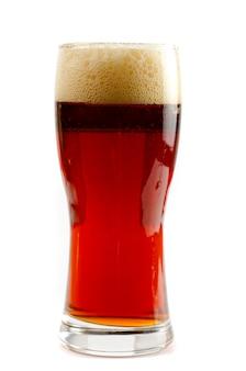 Glas donker bier dat op een witte ruimte wordt geïsoleerd