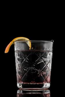 Glas drank met oranje plak en zwarte achtergrond
