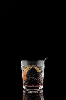 Glas drank met oranje plak in het donker