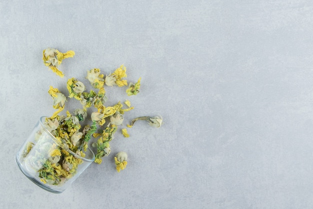 Glas droge chrysant bloemen op stenen tafel.
