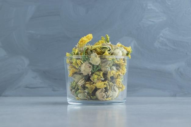 Glas droge chrysantenbloemen op stenen oppervlak