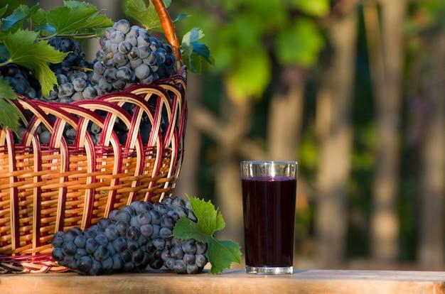 Glas druivensap met druiven rieten mand