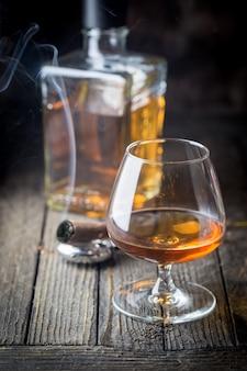Glas en een fles cognac of cognac en rokende sigaar op de houten tafel.