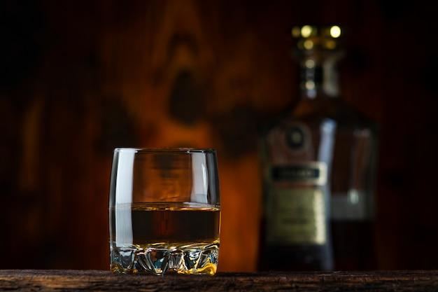 Glas en fles cognac op de tafel. oude houten achtergrond.