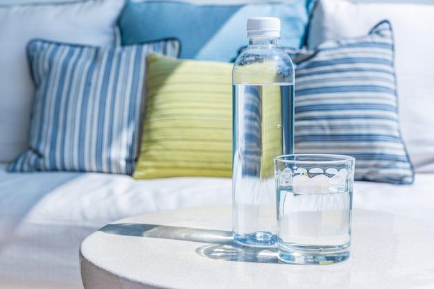 Glas en fles drinkwater op een openluchtlijst op zonnige dag