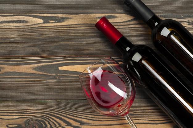 Glas en fles met rode wijn op houten achtergrond, bovenaanzicht
