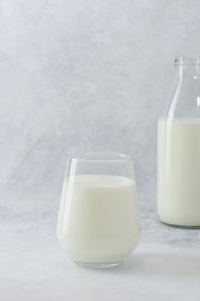 Glas en fles met verse melk op lichte achtergrond met kopie ruimte. zuivelproducten.