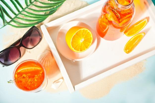 Glas en fles met verse zelfgemaakte oranje zoete ijsthee of cocktail, limonade met tijm. verfrissend koud drankje. zomerfeest.