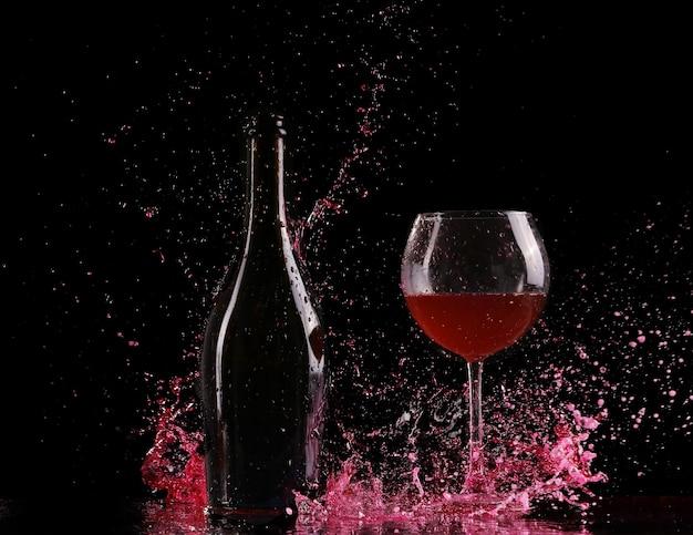 Glas en fles rode wijnplons op zwart