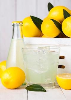 Glas en fles van biologische vers citroensap met rauwe citroenen in witte houten doos