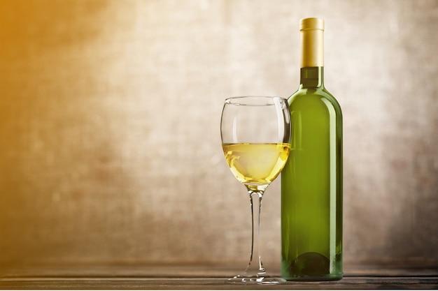 Glas en fles witte wijn op grungeachtergrond