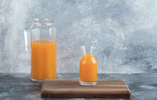Glas en kruik sinaasappelsap op een houten bord.