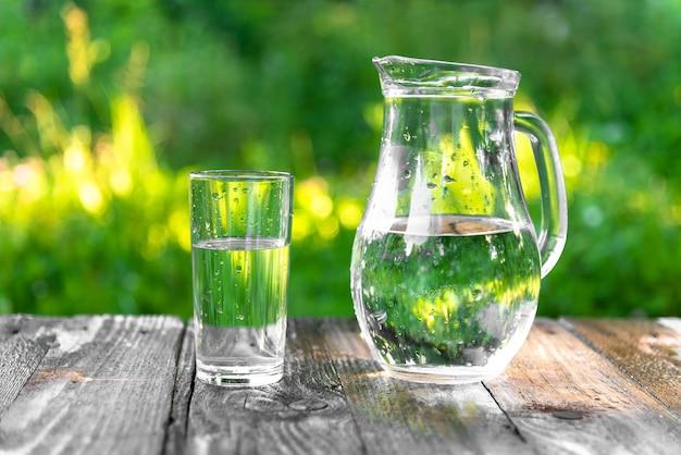Glas en kruik water op tafel tegen de achtergrond van de natuur.