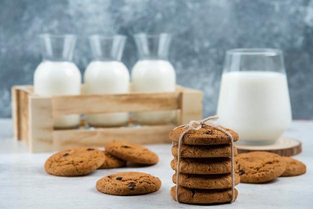 Glas en pot melk met stapel koekjes op marmeren tafel.