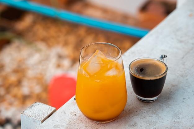 Glas espresso met jus d'orange op houten tafel en kopieer de ruimte, zomercocktail, koud gezette koffie of zwarte thee. (close-up, selectieve focus),