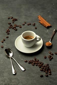 Glas espresso op grijze achtergrond die met koffiebonen wordt verfraaid