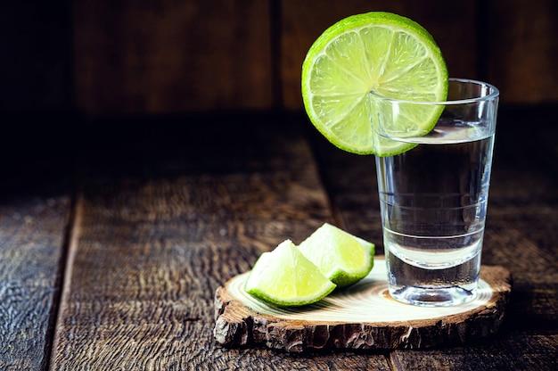 Glas gedistilleerde alcohol, cognac, met citroen, kopie ruimte