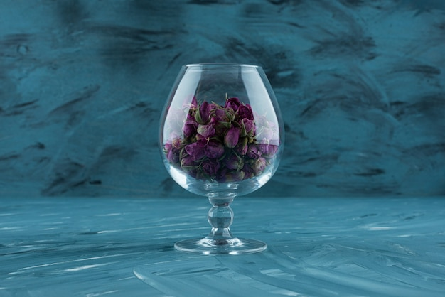 Glas gedroogde paarse rozen op blauwe ondergrond.