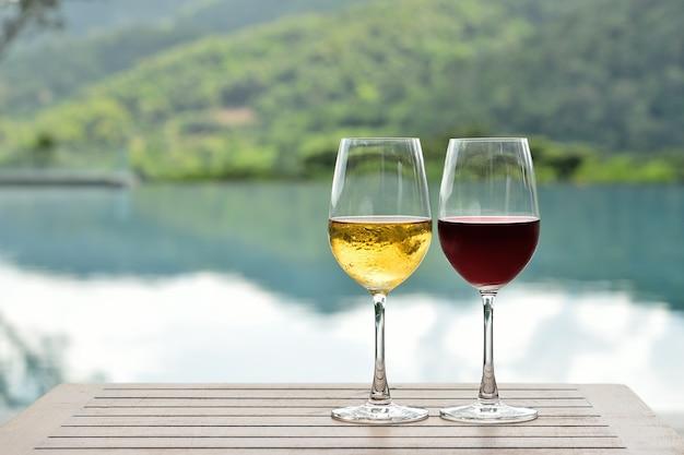 Glas gekoelde witte en rode wijn op tafel bij het zwembad