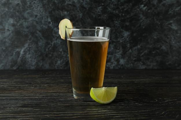 Glas gemberbier en ingrediënt op houten lijst