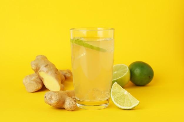 Glas gemberbier en ingrediënten op geel