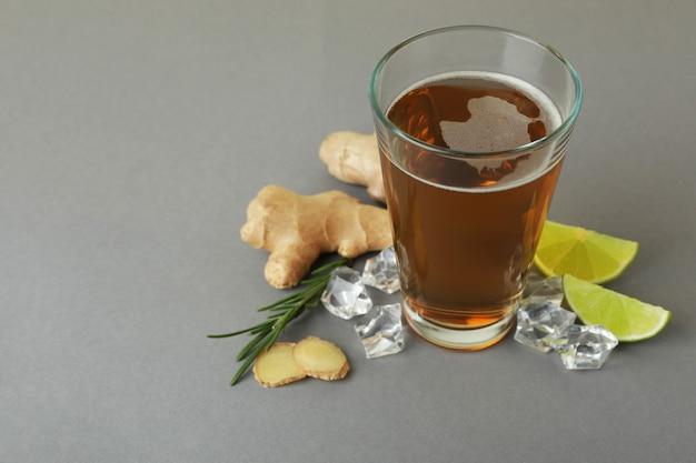 Glas gemberbier en ingrediënten op grijs