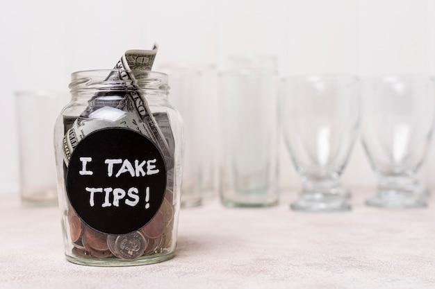 Glas gevuld met geld en lege glazen op de achtergrond