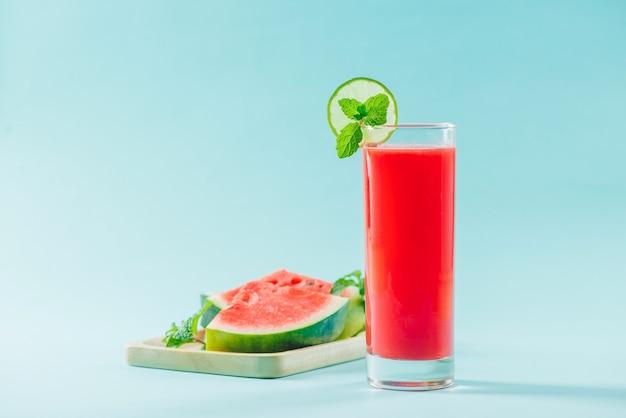 Glas gezond watermeloensap in de zomer op blauwe achtergrond.