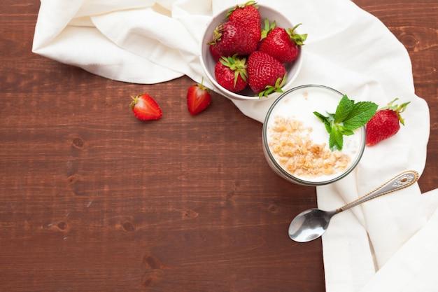 Glas gezonde aardbeiyoghurt met verse bessen op de houten mening van de lijstbovenkant