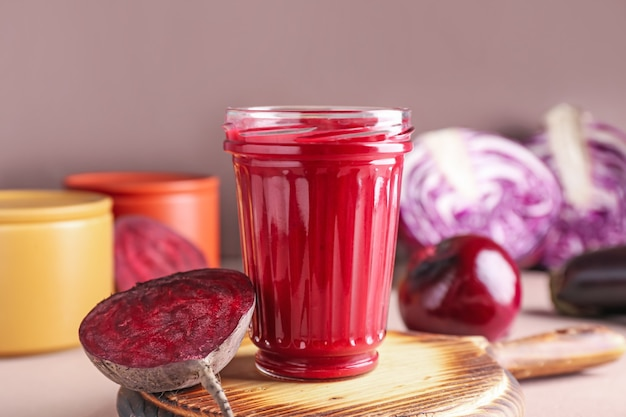 Glas gezonde smoothie en groenten op kleuroppervlak